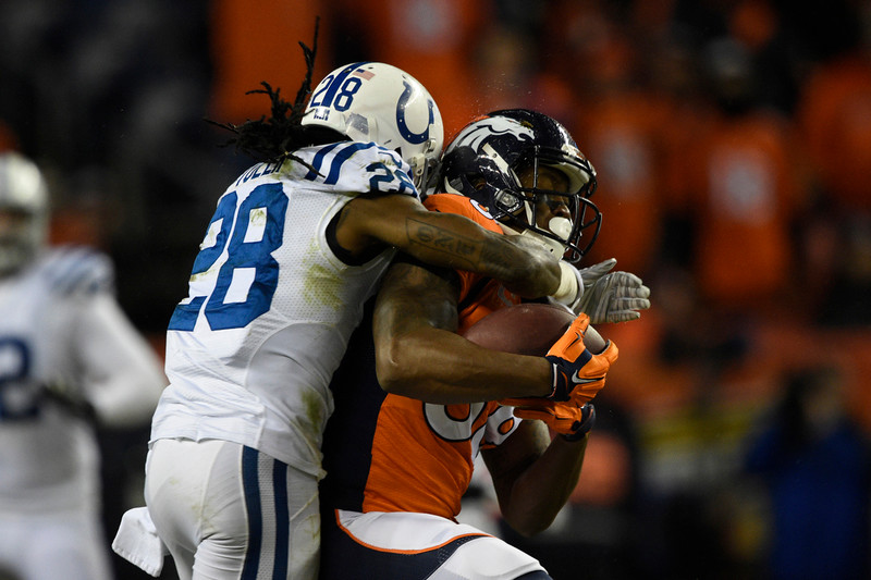 . Demaryius Thomas (88) of the Denver Broncos is hit by Greg Toler (28) of the Indianapolis Colts in the fourth quarter. The Denver Broncos played the Indianapolis Colts in an AFC divisional playoff game at Sports Authority Field at Mile High in Denver on January 11, 2015. (Photo by John Leyba/The Denver Post)