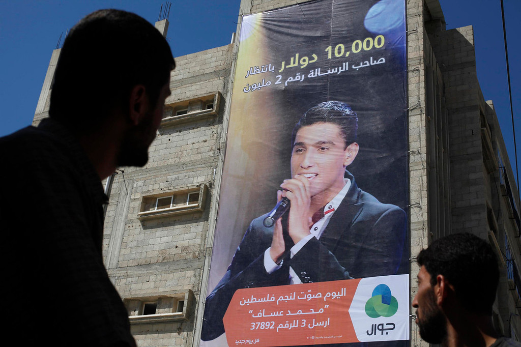 ". Palestinians look at a large poster depicting singer Mohammed Assaf in Khan Younis, in the southern Gaza Strip on June 20, 2013. Palestinian fans and big business are rallying behind Assaf, a 23-year-old singer from the Gaza Strip, in a final push to vote him the next ""Arab Idol\"" in a TV talent contest choosing a winner in Beirut on Saturday. The Arabic words on the bottom of the poster read: \""Vote for the star of Palestine Mohammed Assaf today\"".  REUTERS/Ibraheem Abu Mustafa"