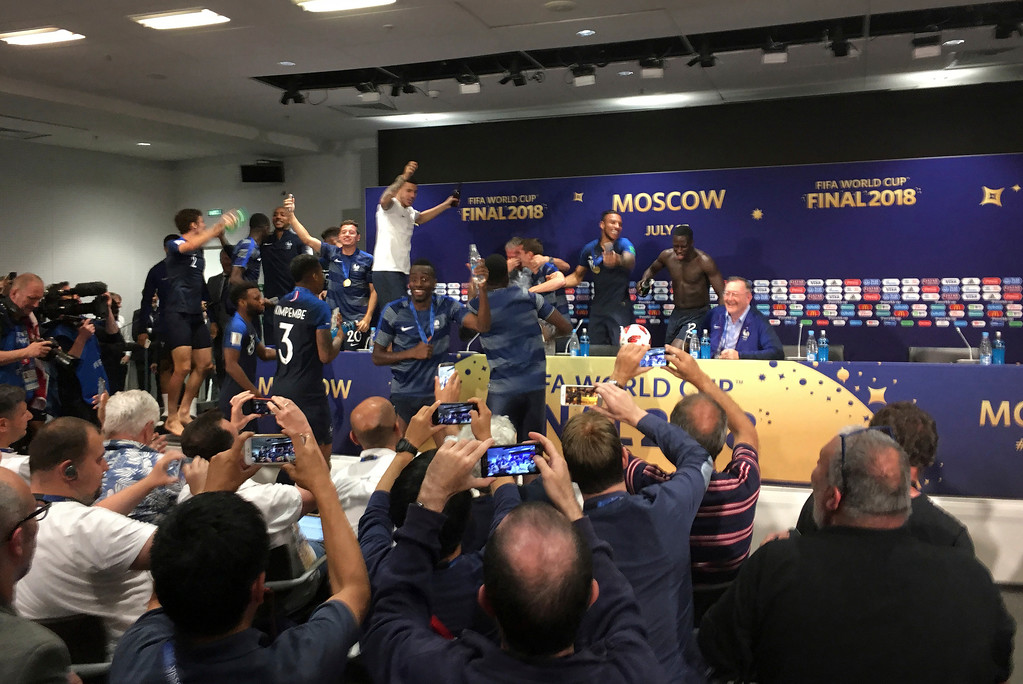 . French players celebrate after bursting into a press conference by France head coach Didier Deschamps after the final match between France and Croatia at the 2018 soccer World Cup in the Luzhniki Stadium in Moscow, Russia, Sunday, July 15, 2018. France won the final 4-2. (AP Photo/Ronald Blum)