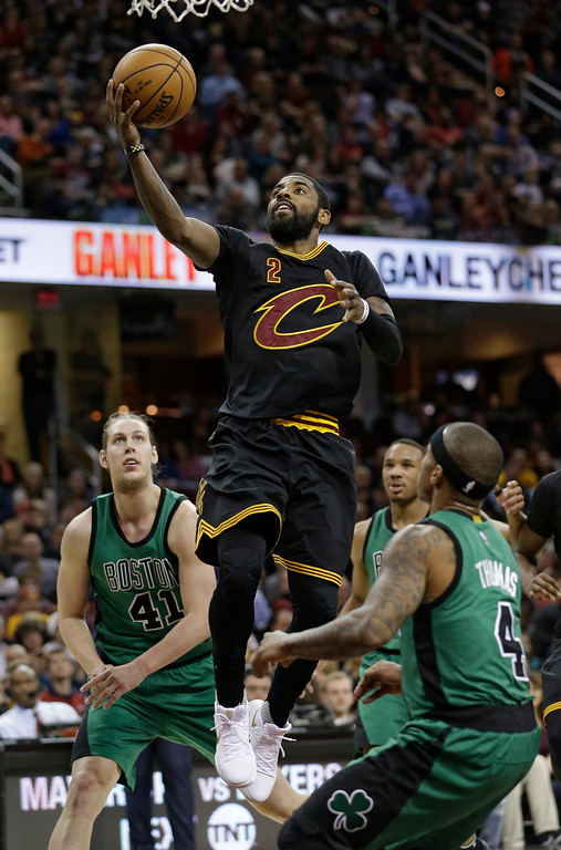 . Cleveland Cavaliers\' Kyrie Irving (2) drives to the basket against Boston Celtics\' Isaiah Thomas (4) and Kelly Olynyk (41) in the second half of an NBA basketball game, Thursday, Dec. 29, 2016, in Cleveland. (AP Photo/Tony Dejak)