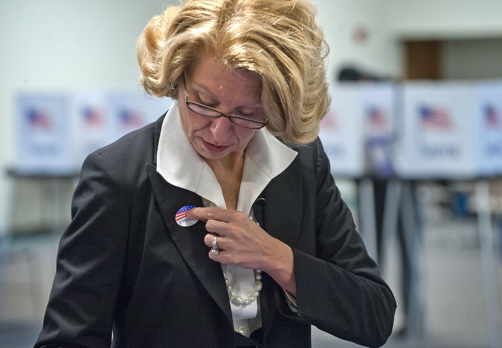 ". State Senate candidate Terri Lynn Land places an ""I voted\"" sticker on her lapel after voting on Election Day at Pathway Church in Byron Center, Mich. Tuesday, Nov. 4, 2014. (AP Photo/The Grand Rapids Press, Chris Clark ) ALL LOCAL TELEVISION OUT; LOCAL TELEVISION INTERNET OUT"