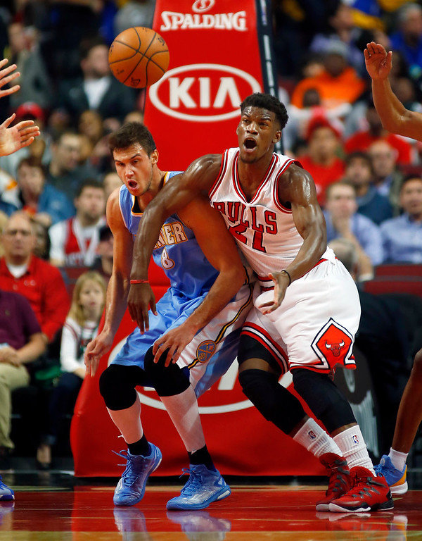 . Chicago Bulls guard Jimmy Butler (21) and Denver Nuggets forward Danilo Gallinari (8) go after the ball during the first half of a pre-season NBA basketball game in Chicago, on Monday Oct. 13, 2014. (AP Photo/Jeff Haynes)