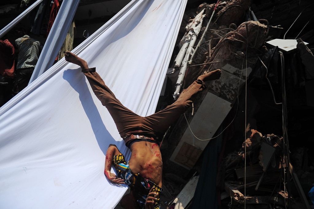 . The dead body of a Bangladeshi garment worker falls after being slid down a length of textile after an eight-story building collapsed in Savar, on the outskirts of Dhaka, on April 24, 2013.  AFP PHOTO/Munir uz  ZAMAN/AFP/Getty Images