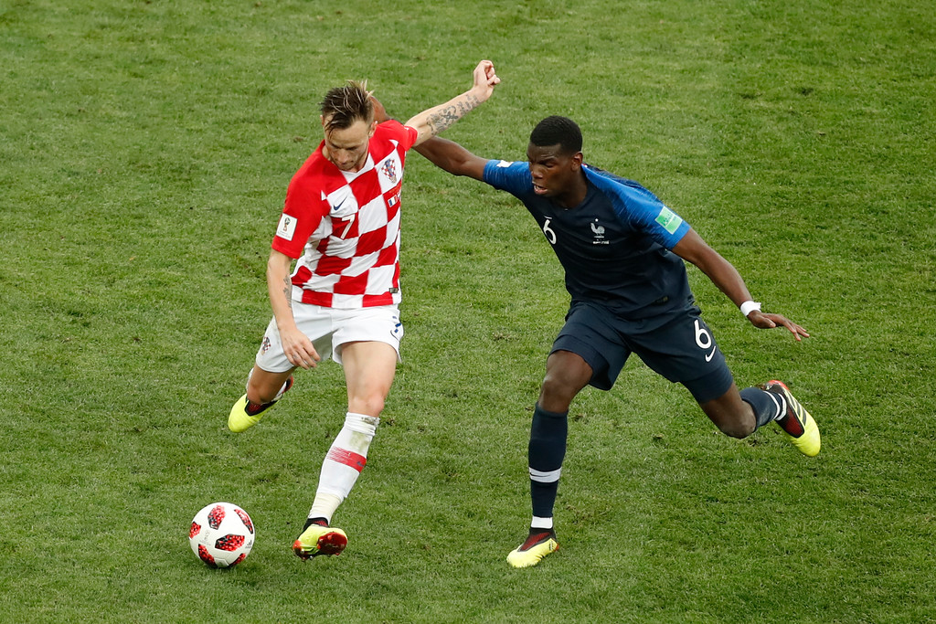 . Croatia\'s Ivan Rakitic, left, and France\'s Paul Pogba challenge for the ball during the final match between France and Croatia at the 2018 soccer World Cup in the Luzhniki Stadium in Moscow, Russia, Sunday, July 15, 2018. (AP Photo/Rebecca Blackwell)