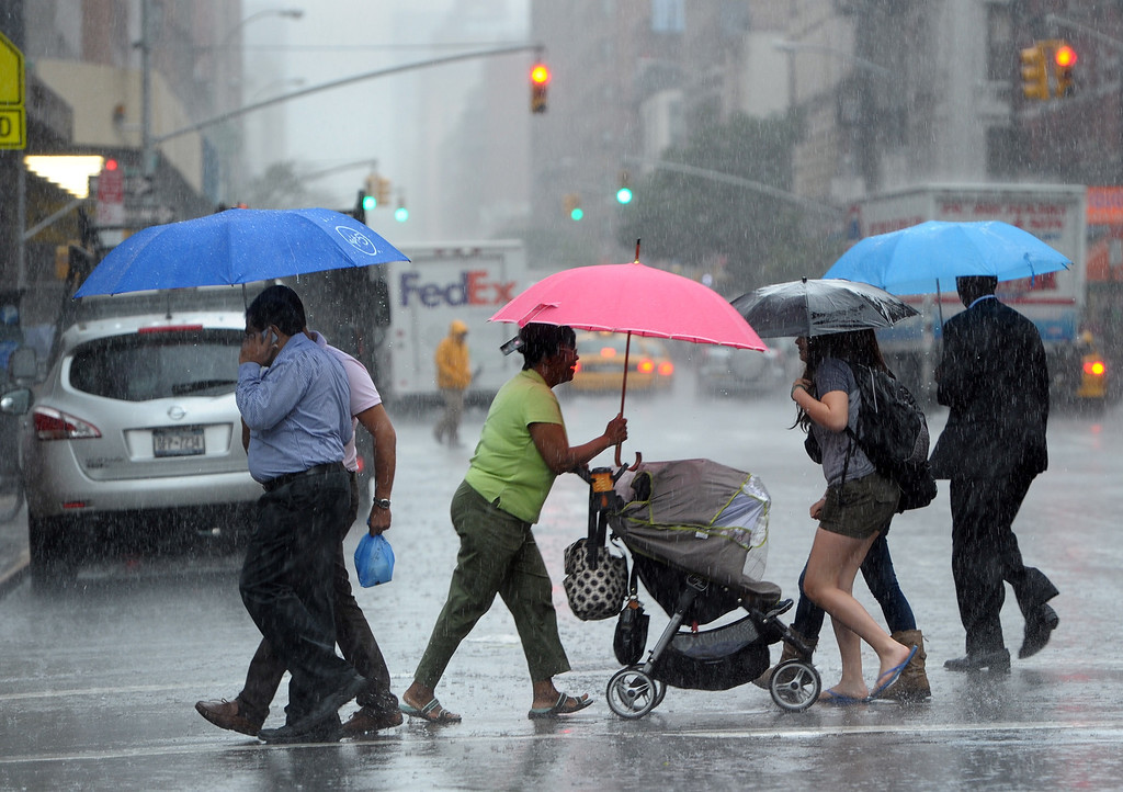 . People on East 86th Street cross Lexingon Avenue in a heavy rain on June 13, 2013 in New York as a severe storm affects the northeastern U.S.  AFP PHOTO/Stan  HONDA/AFP/Getty Images