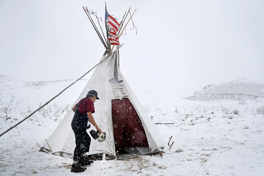""". Vietnam veteran Allen Coomsta Matt walks into his teepee at the Oceti Sakowin camp where people have gathered to protest the Dakota Access oil pipeline as snow begins to fall in Cannon Ball, N.D., Monday, Dec. 5, 2016. \""""I\'ve been living in teepees all my life,\"""" said Matt. \""""People look at me and have no idea what I am. This is all I need,\"""" he added about staying through this week\'s snowfall and freezing temperatures. (AP Photo/David Goldman)"""