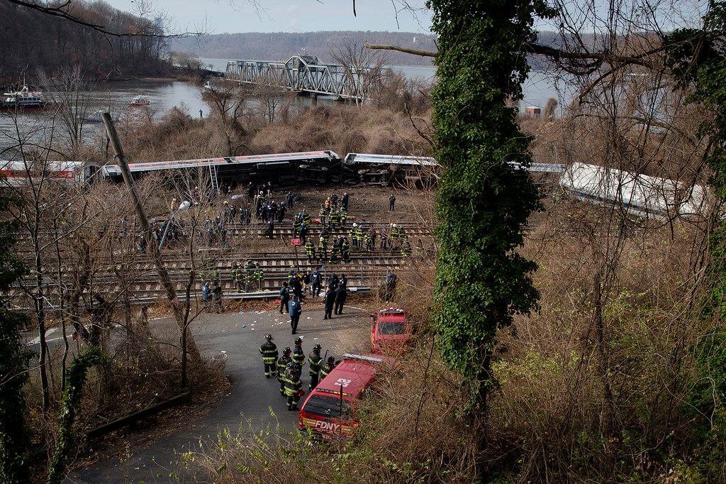 . Emergency personnel work the scene of a Metro-North passenger train derailment in the Bronx borough of New York, Sunday, Dec. 1, 2013. The train derailed on a curved section of track on Sunday morning, coming to rest just inches from the water and causing multiple fatalities and dozens of injuries, authorities said. Metropolitan Transportation Authority police say the train derailed near the Spuyten Duyvil station. (AP Photo/John Minchillo)