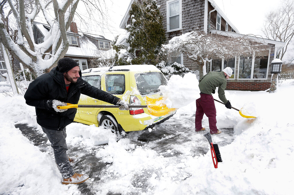. Nicholas Vecchione, left, and Shaun Lewis, right, both of Falmouth, Mass., shovel out a neighbor\'s car, Sunday, Jan. 24, 2016, in Falmouth. A massive winter storm buried much of the U.S. East Coast in a foot or more of snow.  (AP Photo/Steven Senne)