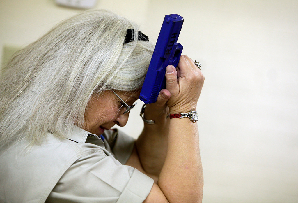 . Arizona Women\'s Shooting Associates and NRA certified instructor Carol Ruh gestures while holding a blue dummy handgun to her head as she teaches a gun safety training class at Ben Avery Shooting Facility in Phoenix, Arizona, March 13, 2013. Ruh educates her students on the proper way to hold, aim, shoot and load a firearm along with other safety tips.  REUTERS/Joshua Lott