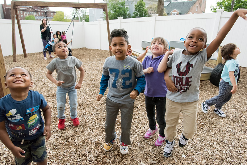 05/20/19  Wesley Bunnell | Staff  Students of the New Britain YMCA School Readiness Program Mason Holmes, Romando Smith, Jeremy Luengas, Josiah Padua and TariQ Ellison reach out to catch bubbles being blown by teacher Emma Wade during outdoor recess.