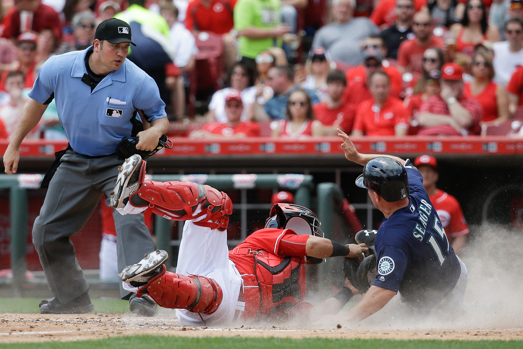 . Seattle Mariners\' Kyle Seager (15) is tagged out by Cincinnati Reds catcher Ramon Cabrera, center, at home plate in the fifth inning of a baseball game, Sunday, May 22, 2016, in Cincinnati. (AP Photo/John Minchillo)