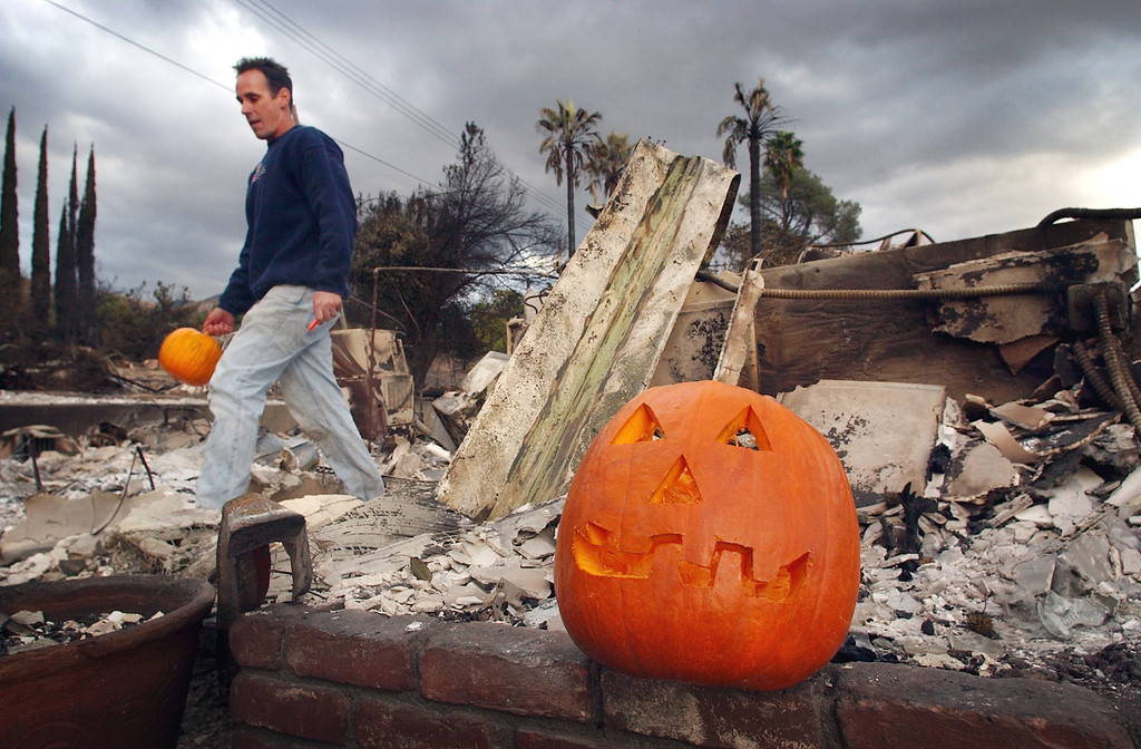 ". Ten years ago this month the arson caused Old Fire, fanned by Santa Ana winds burned thousands of acres, destroyed hundreds of homes and caused six deaths. The fire burned homes in San Bernardino, Highland, Cedar Glen, Crestline, Running Springs and Lake Arrowhead and forced the evacuation of thousand of residents. Todd Stewart brings out a pumpkin from the back yard to curb and places it in front of his mother\'s home along Del Rosa Avenue, in San Bernardino. ""Every year since 1971 there have been two jack-o-lanterns in front of our house,\"" Stewart said. (Staff file photo/The Sun)"