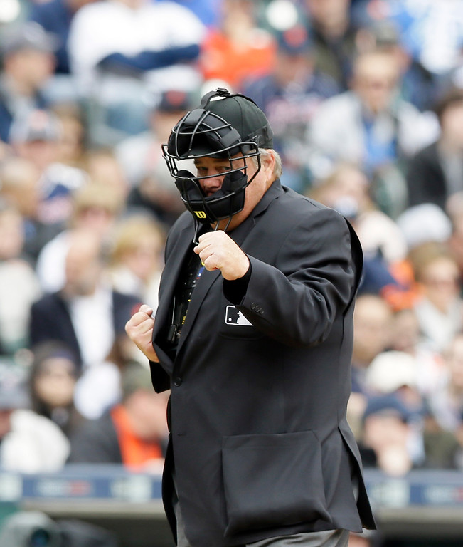 . Homeplate umpire Joe West calls a strike out during the fifth inning of an opening day baseball game between the Detroit Tigers and the Minnesota Twins in Detroit, Monday, April 6, 2015. (AP Photo/Carlos Osorio)