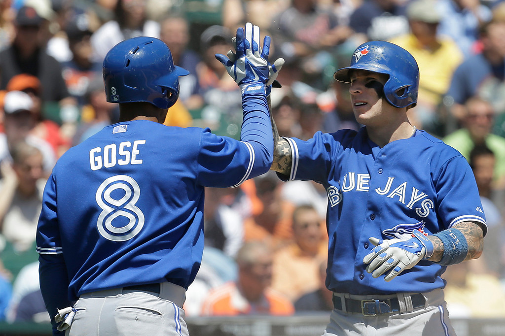 . Toronto Blue Jays\' Anthony Gose (8) congratulates Brett Lawrie who scored on a Erik Kratz single in the fourth inning of a baseball game in Detroit, Thursday, June 5, 2014. (AP Photo/Paul Sancya)