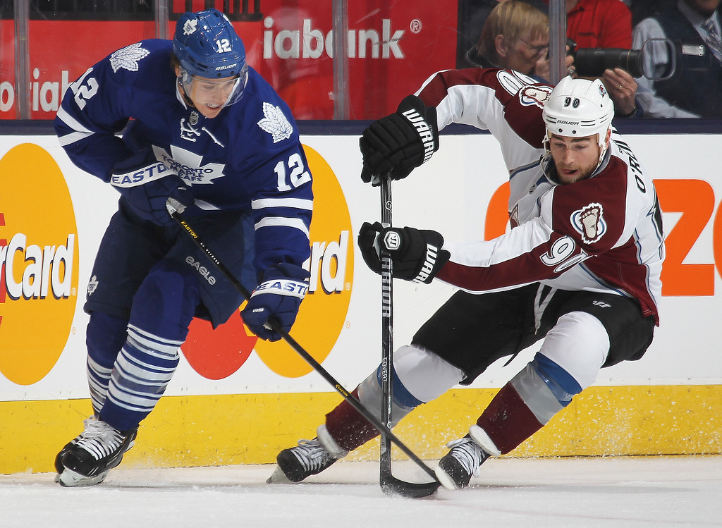 . Ryan O\'Reilly #90 of the Colorado Avalanche battles against Mason Raymond #12 of the Toronto Maple Leafs during an NHL game at the Air Canada Centre on October 8, 2013 in Toronto, Ontario, Canada. (Photo by Claus Andersen/Getty Images)