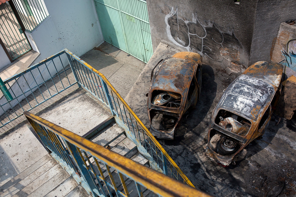 """. In this May 11, 2016 photo, two burnt out Volkswagen Beatle shells, colloquially referred to as \""""Vochos\"""", sit near an overpass on a road leading to the neighborhoods overlooking Acapulco, Mexico. According to neighbors the cars were set on fire about two years ago, during a shootout. (AP Photo/Enric Marti)"""
