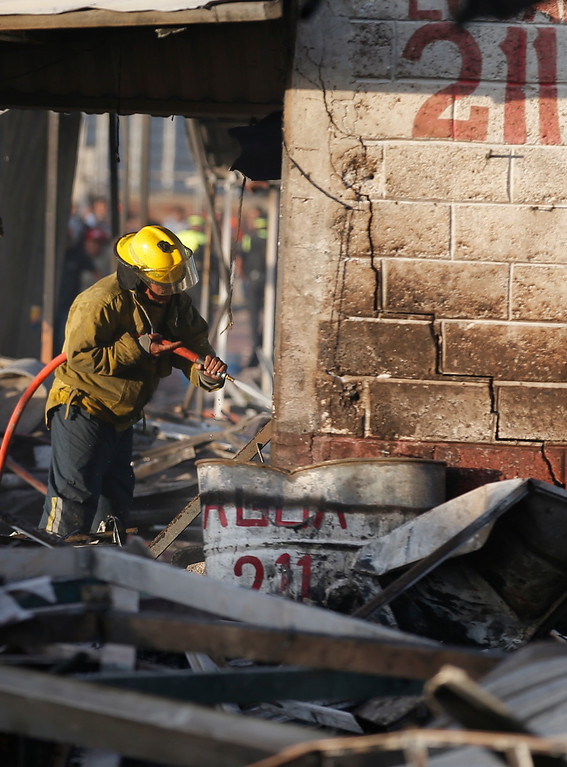 . A fireman sprays water at the open-air San Pablito fireworks market, in Tultepec, outskirts of Mexico City, Mexico, Tuesday, Dec. 20, 2016.  An explosion ripped through Mexico�s best-known fireworks market where most of the fireworks stalls were completely leveled. According to the Mexico state prosecutor there are dozens dead. (AP Photo/Eduardo Verdugo)
