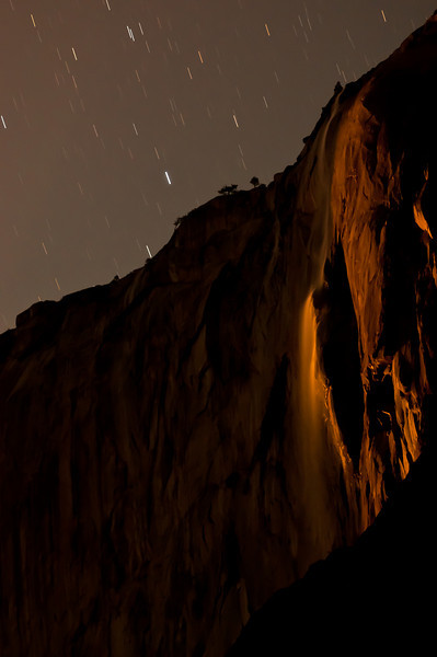 """Many photographers know about Horsetail Falls in Yosemite and that every February it lights up into a """"Fire Falls."""" In fact, I photographed this exact event in February of this year and it was spectacular. Many photographers, however, do not know that the same phenomenon occurs via moonlight on some rare occasions!   On Saturday, Feb 16th 2011 I woke up at 3am and headed over to the Picnic Grounds at Yosemite National Park. When I arrived the moon was really lighting up the falls but the angle wasn't quite right to turn the falls red. After a couple minutes of setting up and figuring out my camera settings all of a sudden the photos started turning orange! It lasted for about 10 minutes before the falls were completely dark.   Note that to the human eye the falls appeared white but to the camera it appeared red! The human eye has 2 photo-receptors: rods and cones. Cones are really good at detail and color but require a lot of light. They don't work so well in low light (night). Rods on the other hand, are really good at low light but they can't detect color. So at night, in this scene, our eye only saw the brightness of the falls but the camera sensor saw the beautiful color!   There is NO saturation change to this. The only thing I did after taking this photo was a small white balance adjustment, some sharpening, and some noise reduction!  I'd also like to note the difficulties in taking this photo. It was nearly pitch black and the camera cannot focus at all. Additionally, using LiveMode, as I did during the sunset Fire Falls, doesn't work either since the LiveMode displayed a completely black view. I had to set the camera to focus at infinity, took a photo, and then tweaked the focus. I continued this until I got a shot that was in focus. Additionally, since there's so little light I had to bump the ISO wayyyyyy up. Additionally, I had to turn """"Long Exposure Noise Reduction"""" and """"High ISO Noise Reduction"""" off or I would have missed out on taking photos of the eve"""