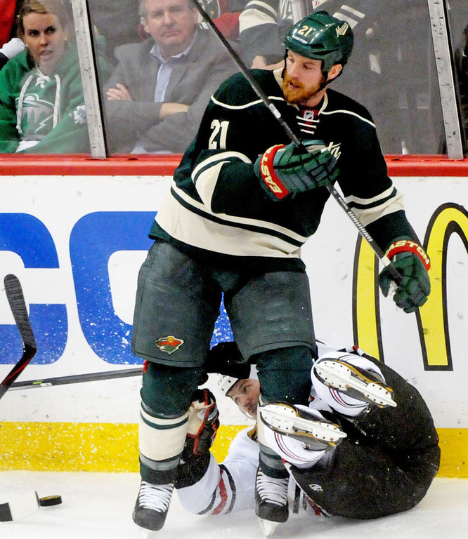 . Minnesota Wild  Kyle Brodziak and Chicago Blackhawks  Sheldon Brookbank  get tangled up along the boards during the third  period of  Game 6 of the Stanley Cup playoffs against the Chicago Blackhawks at Xcel Energy Center Arena on May 13, 2014 in St. Paul.   (Pioneer Press: Sherri LaRose-Chiglo)