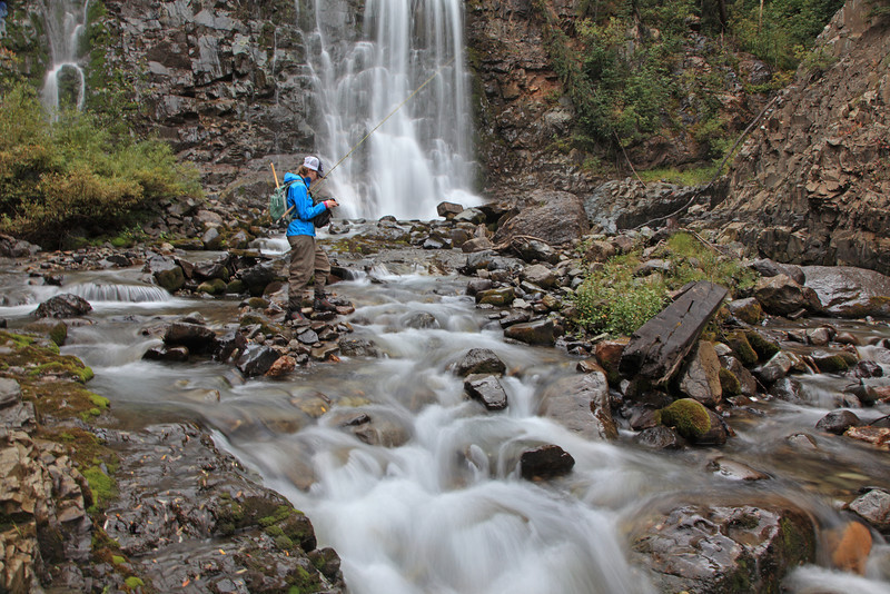 A female fly fisherman at a high mountain waterfall going near Telluride, CO