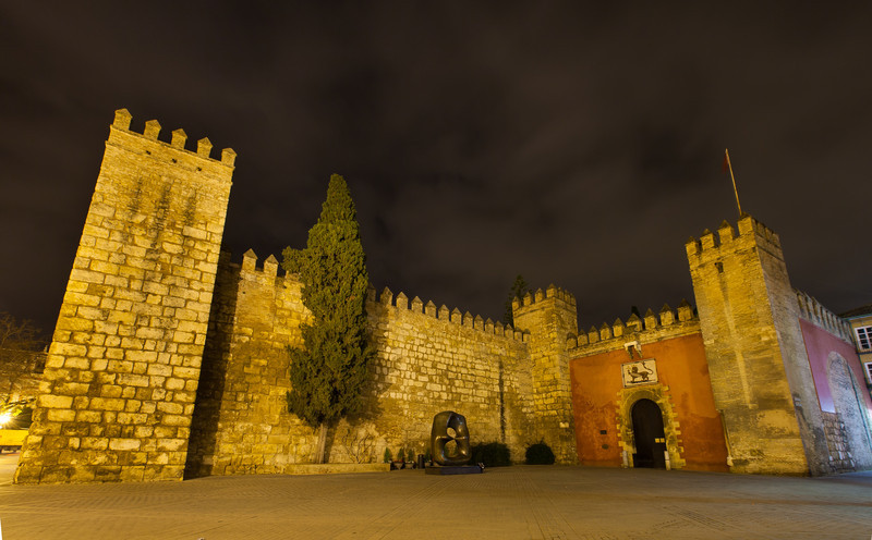 A nighttime view of the entrance of the Alcázar.