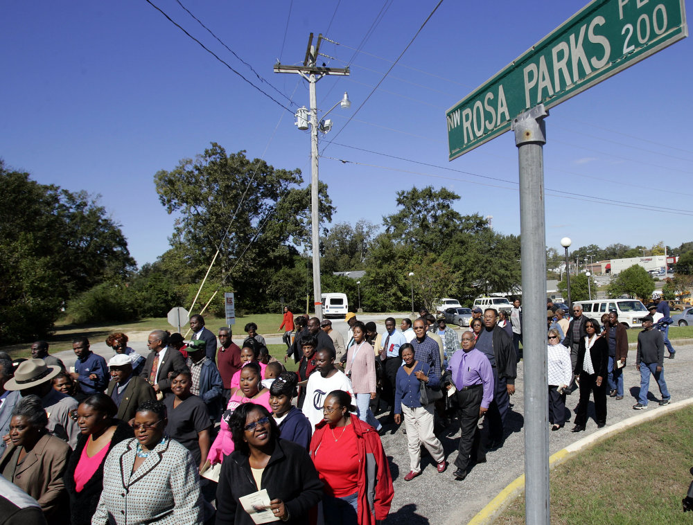 Description of . Marchers pass by a street sign honoring Rosa Parks during a memorial service for her Wednesday Oct. 26, 2005 in Tuskegee, Ala. Parks, 92, a native of Tuskegee, died earlier in the week at her home in Detroit. (AP Photo/Rob Carr)