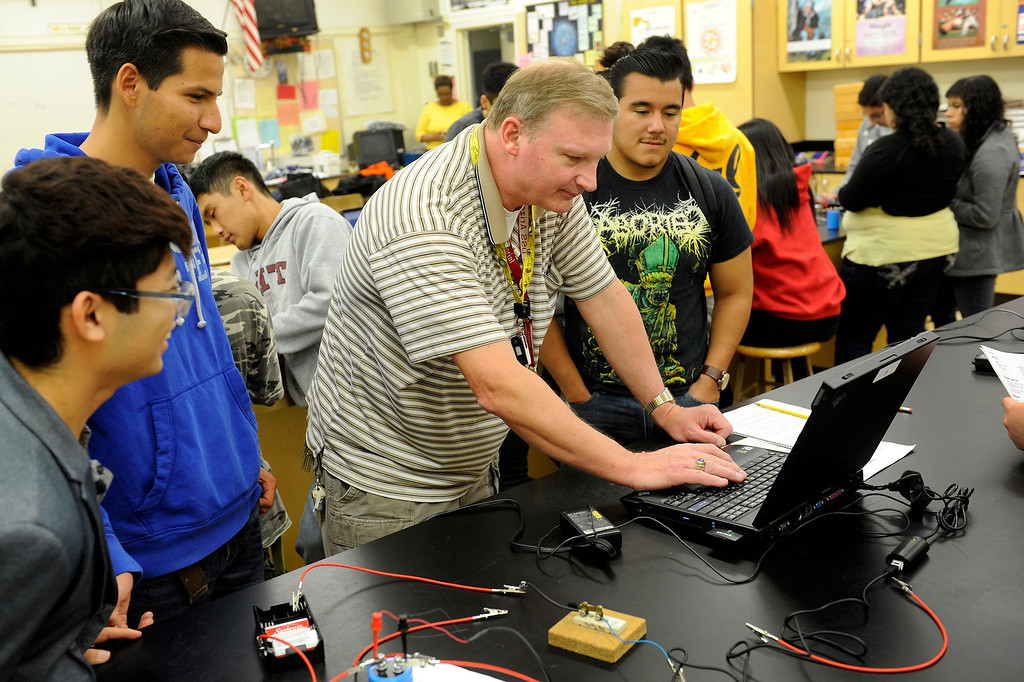 . Poly High School physics teacher Jim Schwagle helps students set up the computer for measuring a capacitor, Wednesday, March 20, 2013. Poly High School will become a pilot school in the Fall when it becomes a pilot school. Pilot schools have greater autonomy over scheduling, curriculum and budgets. (Michael Owen Baker/Staff Photographer)
