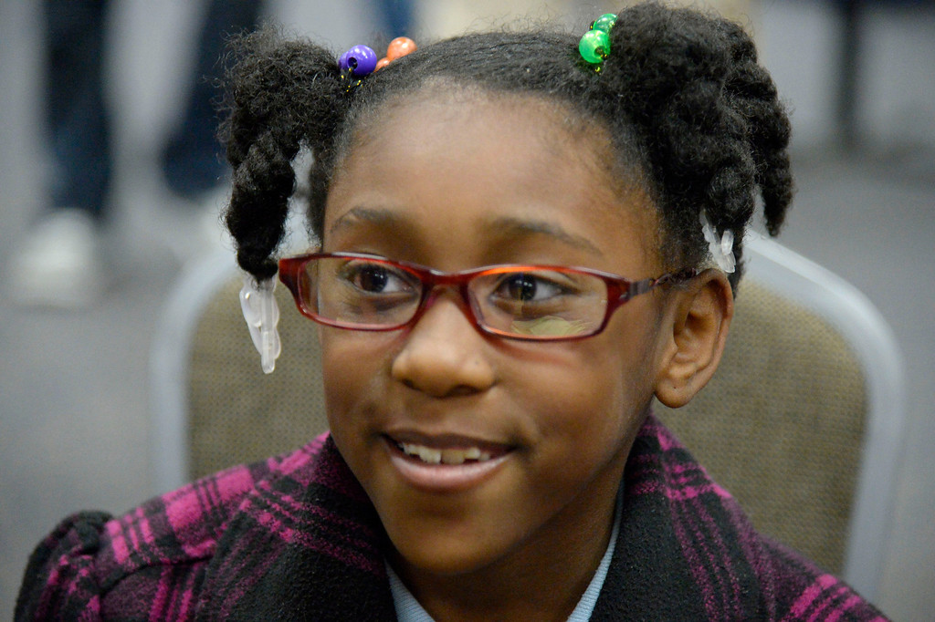 . Myreonna Evans, 9, smiles after getting her prescription glasses.   (Photo by John Leyba/The Denver Post)