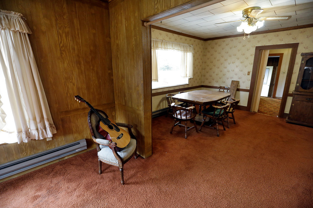 . This photo taken Monday, Sept. 23, 2013, shows a guitar, staged for the home sale, and the dining room table and hutch from when Kurt Cobain, the late frontman of Nirvana, lived there in Aberdeen, Wash. (AP Photo/Elaine Thompson)