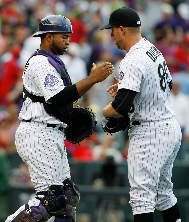 . Colorado Rockies catcher Wilin Rosario, left, congratulates relief pitcher Josh Outman after he retired the Philadelphia Phillies in the ninth inning of a baseball game in Denver on Saturday, June 15, 2013.  The Rockies won 10-5.  (AP Photo/David Zalubowski)