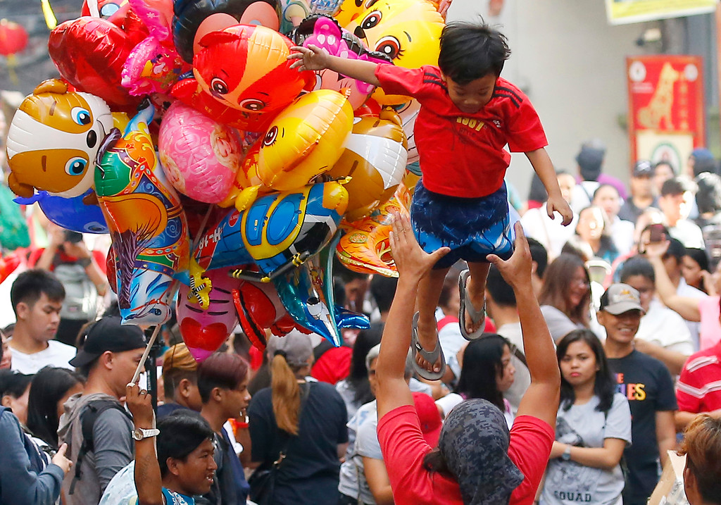 . A father tosses his son in the air as Filipinos gather at Manila\'s Chinatown district, Philippines in celebration of the Chinese Lunar New Year Friday, Feb. 16, 2018. This year is the Year of the Dog in the Chinese Lunar calendar. (AP Photo/Bullit Marquez)