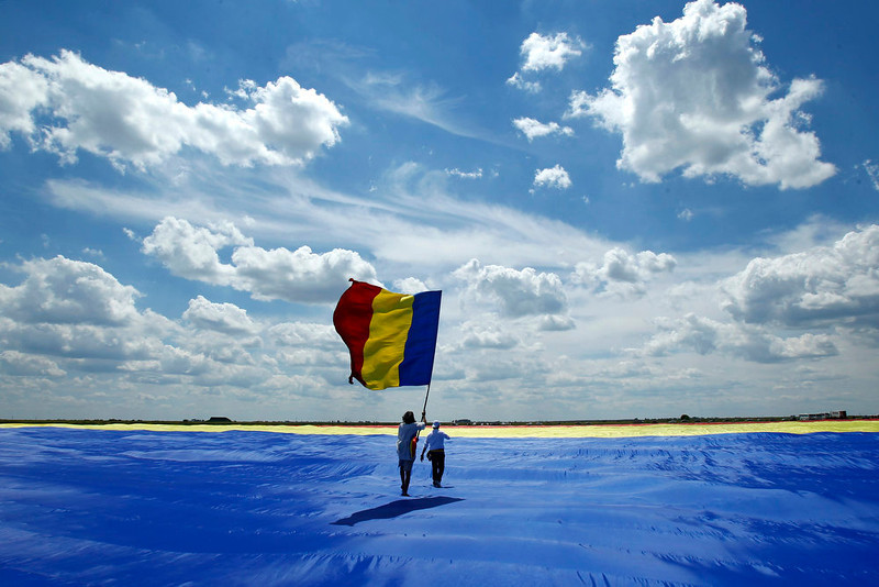 . Two men walk on Romania\'s national flag during a Guinness World Record attempt for the world\'s biggest national flag in Clinceni, near Bucharest May 27, 2013.  The flag, measuring 349.4 per 226.9 meters, established a new Guinness World Record, according to the organization\'s officials. REUTERS/Bogdan Cristel