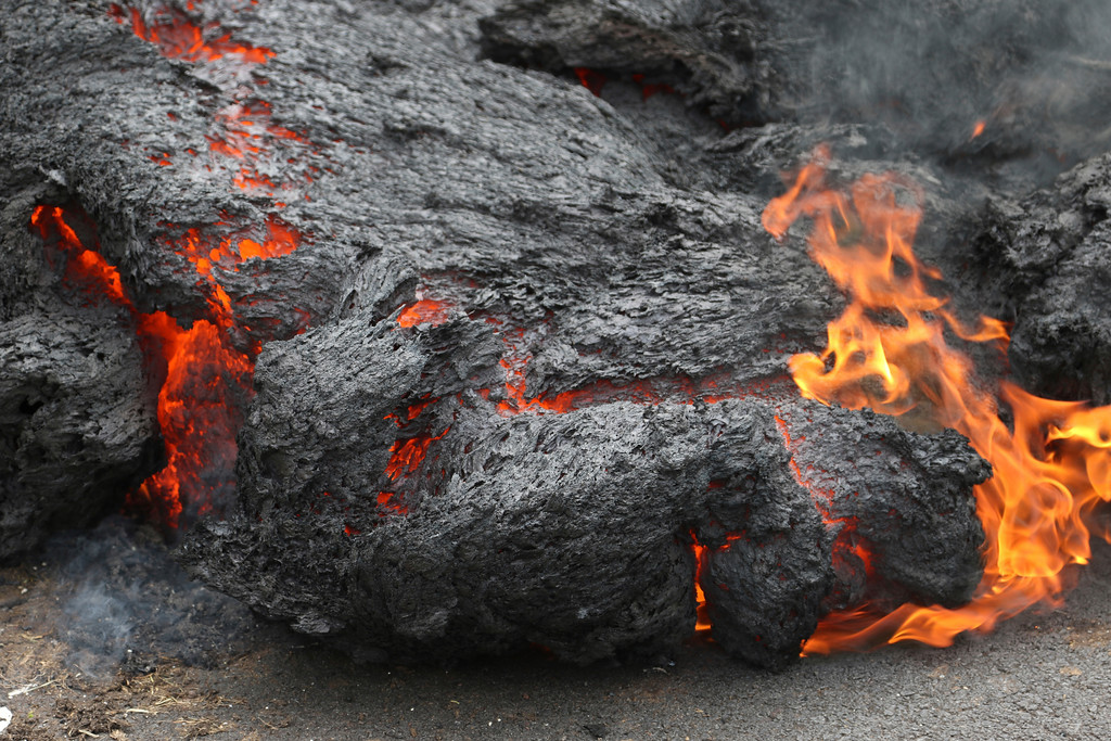. Lava burns across a road in the Leilani Estates subdivision on Saturday, May 5, 2018, near Pahoa, Hawaii. Glowing plumes of lava have shot hundreds of feet into the air at points, officials said, and black-and-orange ribbons of rock have curled into roadways. (AP Photo/Caleb Jones)