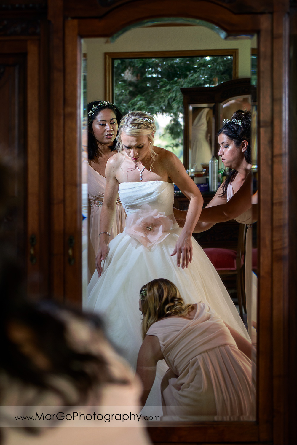 mirror shot of bride getting ready with bridesmaids