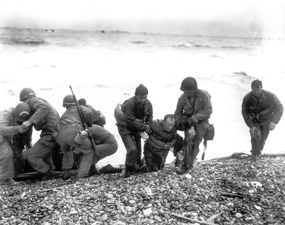 . Members of an American landing unit help their exhausted comrades ashore during the Normandy invasion, June 6, 1944. The men reached the zone code-named Utah Beach, near Sainte Mere Eglise, on a life raft after their landing craft was hit and sunk by German coastal defenses.  (AP Photo)