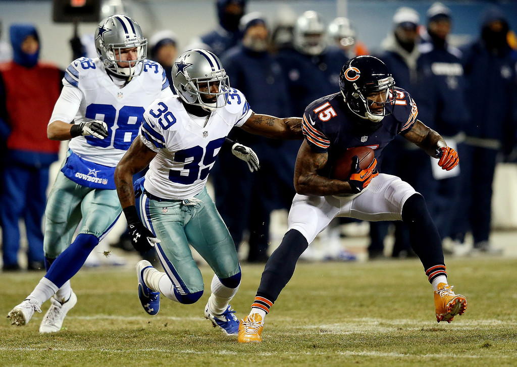 . Wide receiver Brandon Marshall #15 of the Chicago Bears tries to avoid a tackle by cornerback Brandon Carr #39 of the Dallas Cowboys during a game at Soldier Field on December 9, 2013 in Chicago, Illinois.  (Photo by Jonathan Daniel/Getty Images)