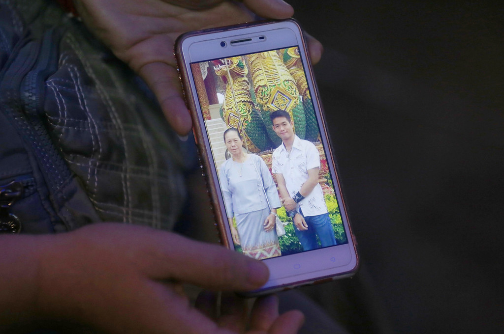 . The aunt of coach Ekapol Chantawong shows a picture of the coach and his grandmother on a mobile phone screen, in Mae Sai, Chiang Rai province, in northern Thailand, Wednesday, July 4, 2018. With heavy rains forecast to worsen flooding in a cave in northern Thailand where 12 boys and their soccer coach are waiting to be extracted by rescuers, authorities say they might be forced to have them swim out through a narrow, underwater passage. The 13 are described as healthy and being looked after by medics inside the cave.(AP Photo/Sakchai Lalit)