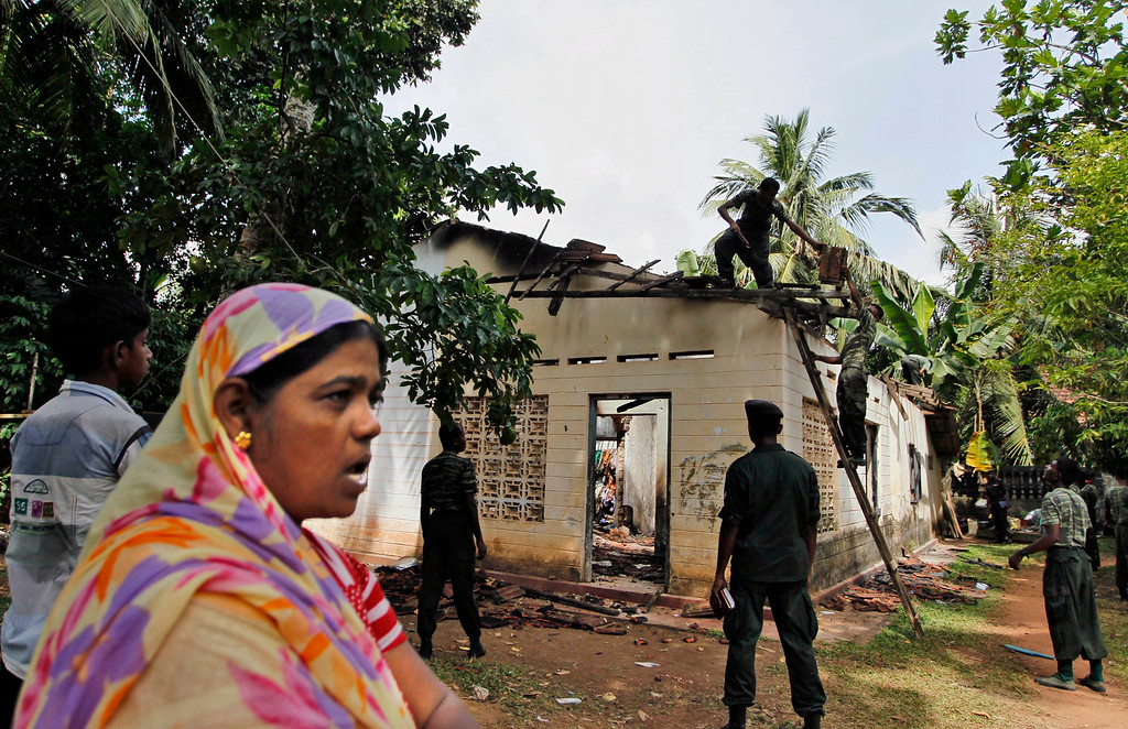 . In this Friday, June 27, 2014 photo, a Sri Lankan Muslim woman watches as army soldiers salvage damaged household items from the debris of a burnt house in Darga Town in Aluthgama, about 50 kilometers (31 miles) south of Colombo, Sri Lanka. The onslaught by the Bodu Bala Sena (BBS), a hardline Buddhist group, killed two Muslims in the worst religious violence Sri Lanka has seen in decades. (AP Photo/Eranga Jayawardena)