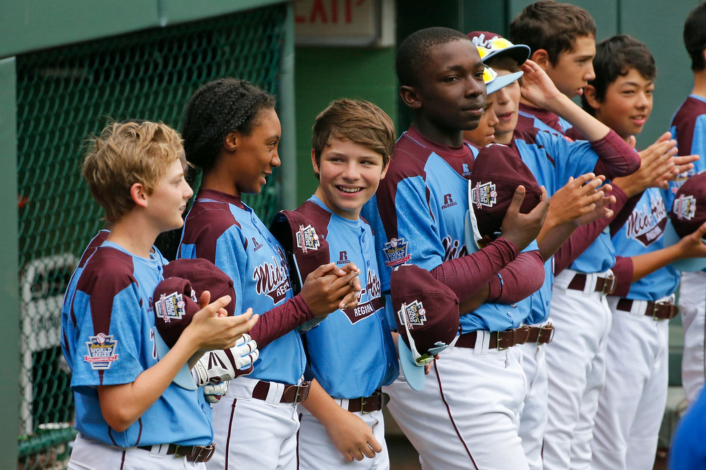 . Philadelphia pitcher Mo\'ne Davis, second from left, stands with her teammates before they played Nashville during a baseball game in U.S. pool play at the Little League World Series tournament in South Williamsport, Pa., Friday, Aug. 15, 2014. Philadelphia won 4-0. (AP Photo/Gene J. Puskar)