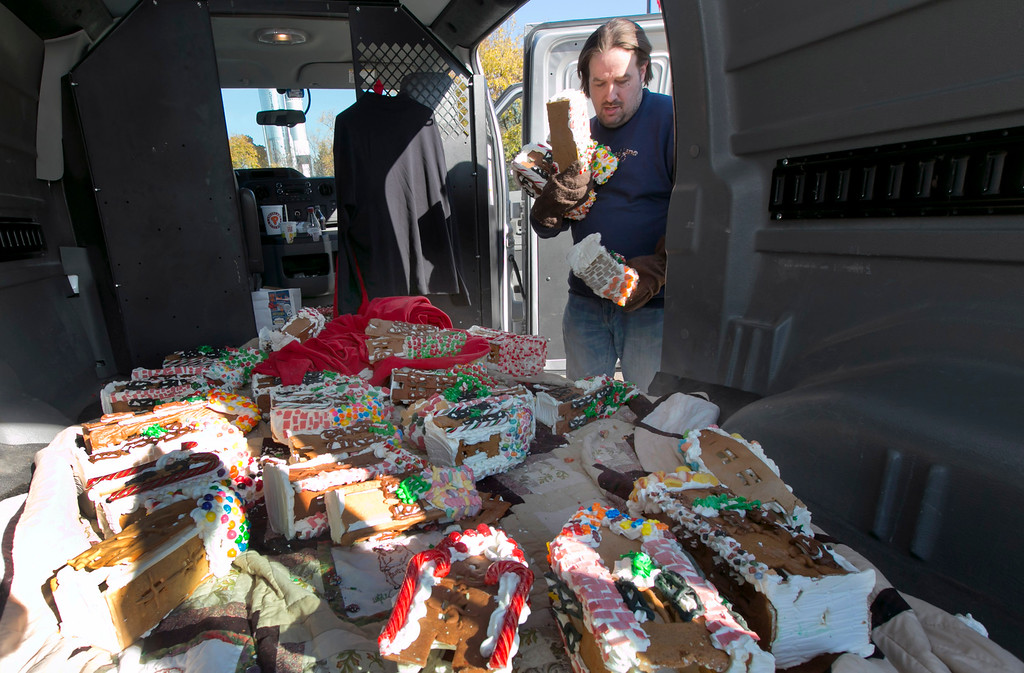 . Chef Jon Lovitch collects some of his gingerbread house creations from his van to add to his GingerBread Lane display, at the New York Hall of Science, in the Queens borough of New York, Thursday, Nov. 13, 2014. Lovitch, a Manhattan chef who holds the Guinness record for creating the world\'s largest collection of gingerbread houses, is now going for another record, competing against himself by assembling more than 1,000 new ones. (AP Photo/Richard Drew)