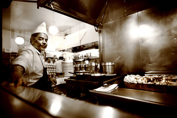 Hamming for the camera, a worker is overseeing the cooking of small mountain of hash browns on the grill.