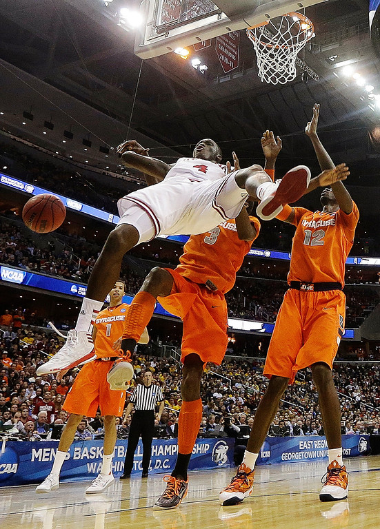 . Indiana guard Victor Oladipo (4) falls in front of Syracuse forward Jerami Grant (3) and center Baye Keita (12) during the first half of an East Regional semifinal in the NCAA college basketball game, Thursday, March 28, 2013, in Washington. (AP Photo/Pablo Martinez Monsivais)