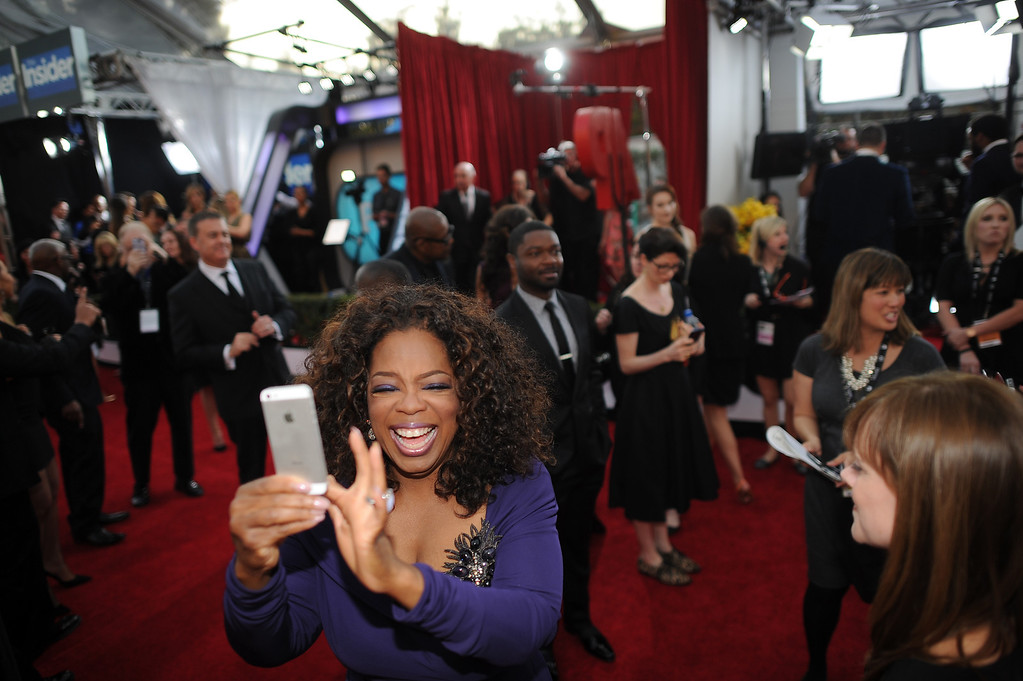 . Oprah Winfrey takes a photo of photographers and fans on the red carpet at the 20th Annual Screen Actors Guild Awards  at the Shrine Auditorium in Los Angeles, California on Saturday January 18, 2014 (Photo by Hans Gutknecht / Los Angeles Daily News)