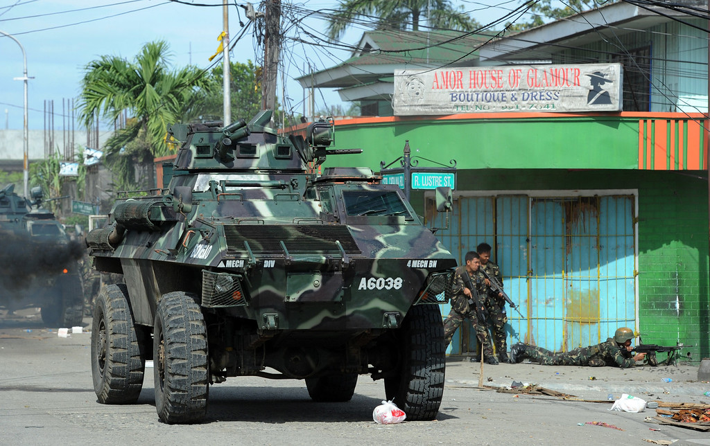 . Philippine soldiers supported by an armored personnel carrier fire towards enemy position during a fire fight between government forces and Muslim rebels as stand-off entered its fourth day in Zamboanga City on the southern island of Mindanao on September 12, 2013. AFP PHOTO/TED ALJIBE/AFP/Getty Images