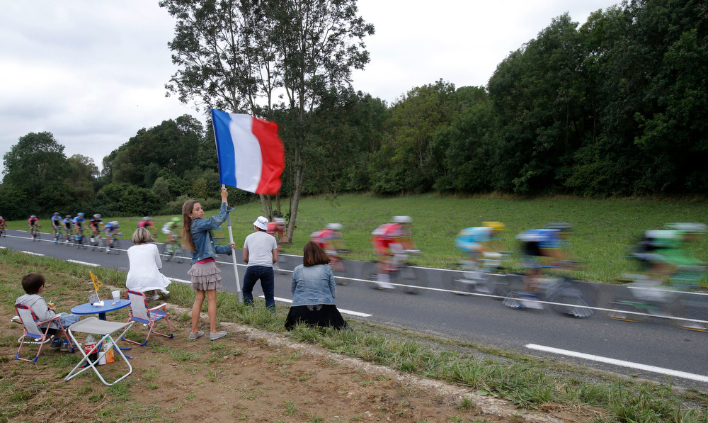 . A girl waves a French flag as the pack passes during the eighth stage of the Tour de France cycling race over 161 kilometers (100 miles) with start in Tomblaine and finish in Gerardmer, France, Saturday, July 12, 2014. (AP Photo/Christophe Ena)
