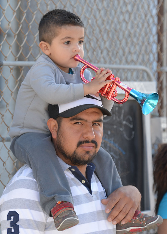 . The 26th Annual Martin Luther King, Jr., Peace & Unity Parade Saturday, January 18, 2014, Long Beach, CA. Jason Reynoso, 2, sits on his dad Marco\'s shoulders and decides to play along with a passing marching band. Photo by Steve McCrank/Daily Breeze