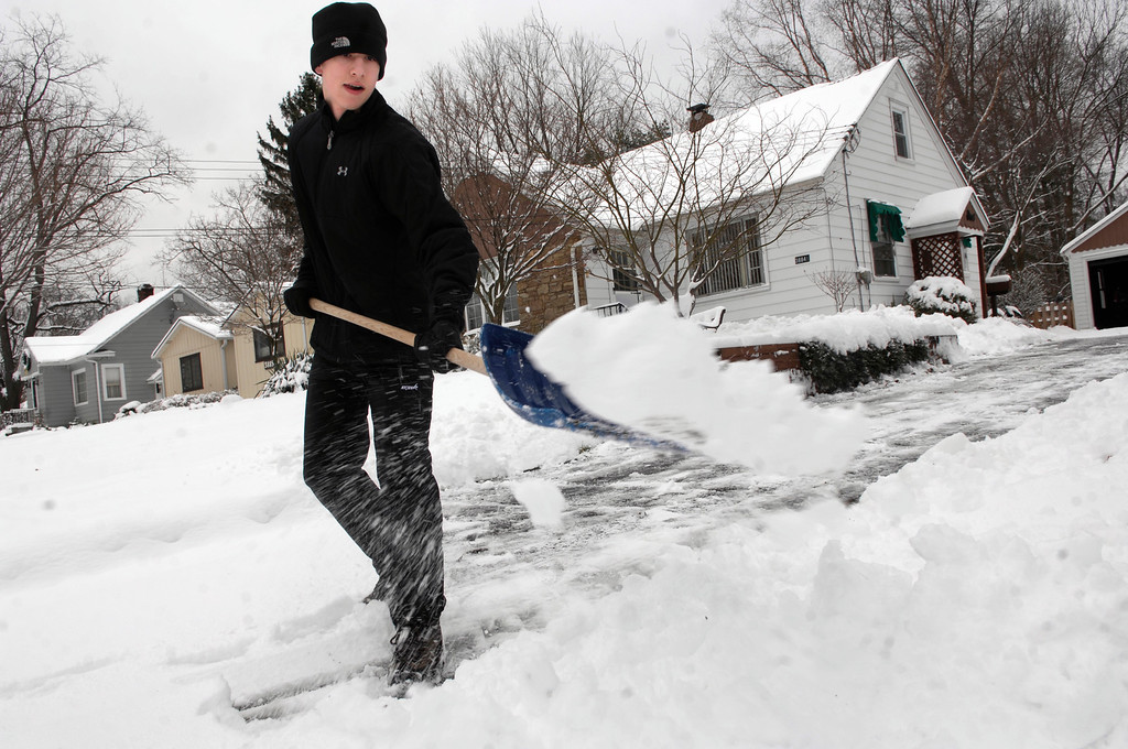 . Sprinkle cat litter or sand on icy patches. Pictured here, Sam Guyett shovels his driveway on Willowdale Drive in Willoughby in December 2012. (News-Herald file)