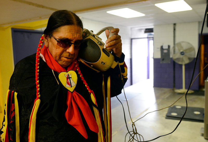 . Kiowa Indian, Tom Ware, master of ceremonies for the 22nd annual Sand Creek Descendants Gathering in Anadarko Oklahoma, listens intently to the 4A Oklahoma State high school football championship between the Anadarko Warriors and the Clinton Red Tornadoes Saturday, December 1st, 2012. Anadarko lost 21-14. Nearly 100 descendants of the Sand Creek Massacre gathered at the Anadarko High School gym for traditional Gourd dancing, food and other activities and also to get updates on legal action towards the U.S. for the massacre which left over 150 Cheyenne and Arapaho Indians dead in southeast Colorado November 29th, 1864. The Denver Post/ Andy Cross