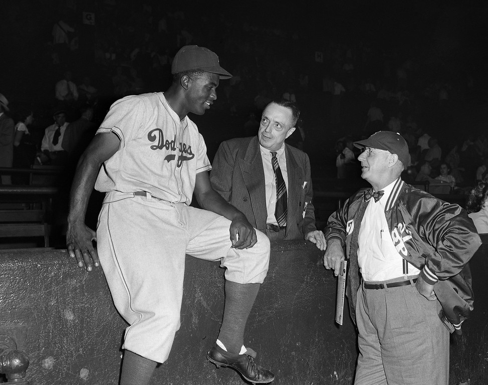 ". Jackie Robinson (left), Brooklyn Dodgers baseman who was named ""Rookie of the Year\"" by Sporting News, a baseball publication,  chats at Sportsmans Park in St. Louis, Sept. 12, 1947 with J.G. Taylor Spink (center), editor of Sporting News, and Dodgers Manager Burt Shotton just before the St. Louis Cardinals-Dodgers game, Sept. 13, 1947. (AP Photo)"