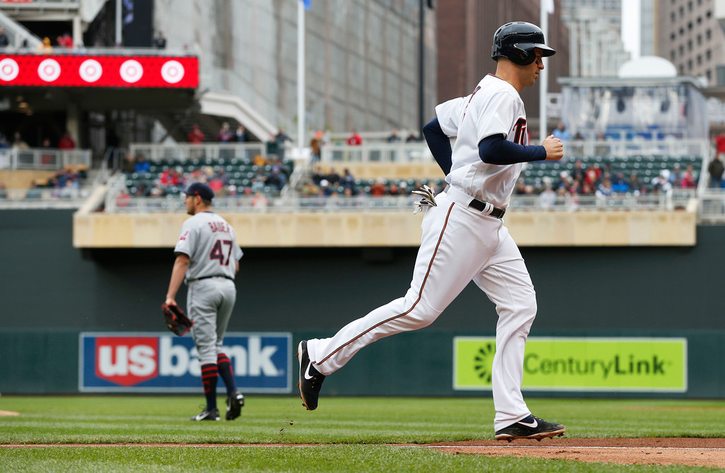 . Minnesota Twins\' Joe Mauer jogs home on a bases-loaded balk by Cleveland Indians pitcher Trevor Bauer, left, in the fourth inning of a baseball game Thursday, April 20, 2017, in Minneapolis. (AP Photo/Jim Mone)